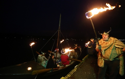 The boat carrying Lucia Bride Rachel Doornink is greeted by the Sons of Norway vikings on the dock of the Poulsbo Marina for the start of Julefest in Poulsbo on Saturday, December 5, 2015. (MEEGAN M. REID / KITSAP SUN)