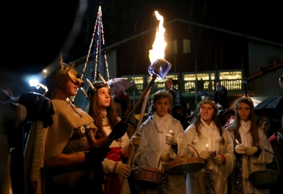 A viking lights the torch of Lucia Bride Rachel Doornink as she prepares to light the bonfire for Julefest in Poulsbo on Saturday, December 5, 2015. (MEEGAN M. REID / KITSAP SUN)